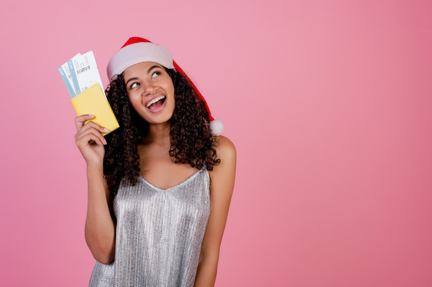 Black woman with plane tickets and passport wearing santa hat Premium Photo