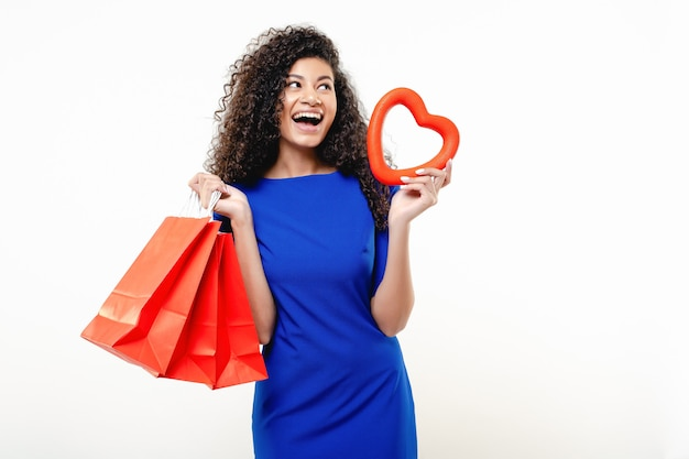 Black woman with red heart shape and shopping bags isolated Premium Photo
