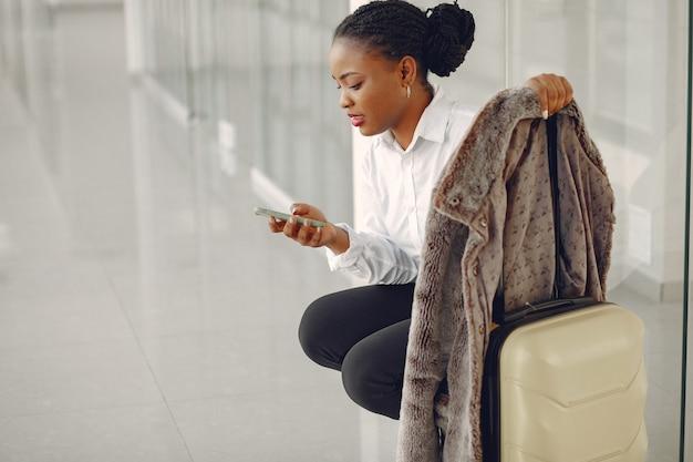 Donna di colore con la valigia in aeroporto Foto Gratuite