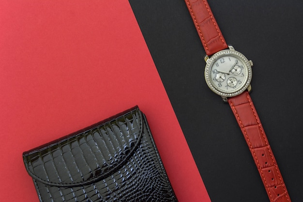 Black women's lacquered leather wallet and women's wrist watch on black and red background Premium Photo