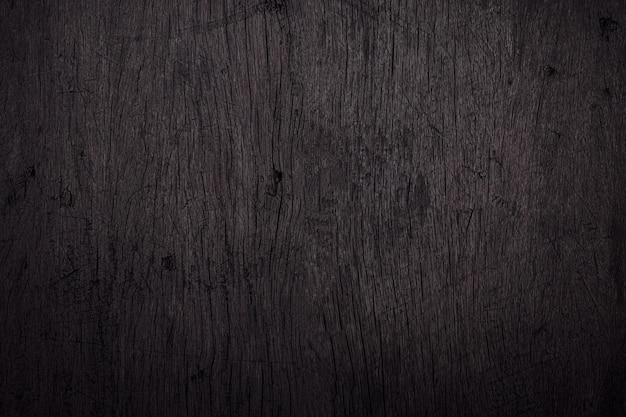 Black wood background with scratches and dust. detail of scratched wooden surface. Premium Photo