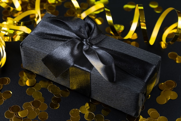 Black wrapped gift with confetti Free Photo