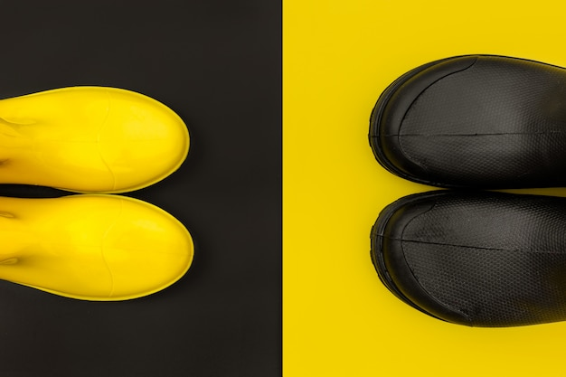Black and yellow rubber boots on yellow and black Premium Photo