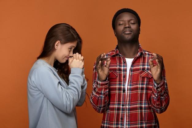 Черный молодой парень, делая жест мудры и с закрытыми глазами, пытается успокоиться, имея спор или несогласие со своей упрямой белой женой. портрет межрасовой пары молится Бесплатные Фотографии