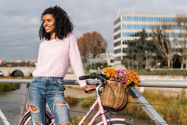 Black young woman riding a vintage bicycle Premium Photo