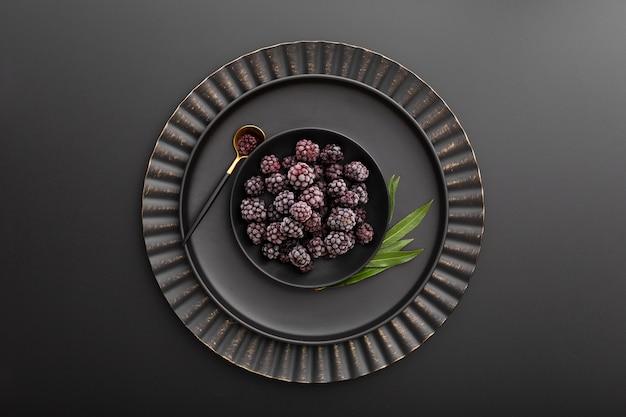 Blackberry bowl on a dark plate on a dark background Free Photo