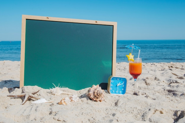Blackboard and cocktail on beach Free Photo