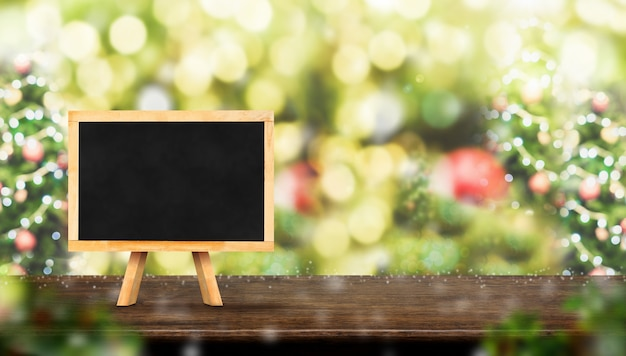 Blackboard on dark brown wood table with abstract blur christmas tree red decor ball and s Premium Photo