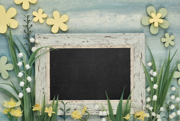 Blackboard framed with spring flowers on neutral background, space for your text Premium Photo