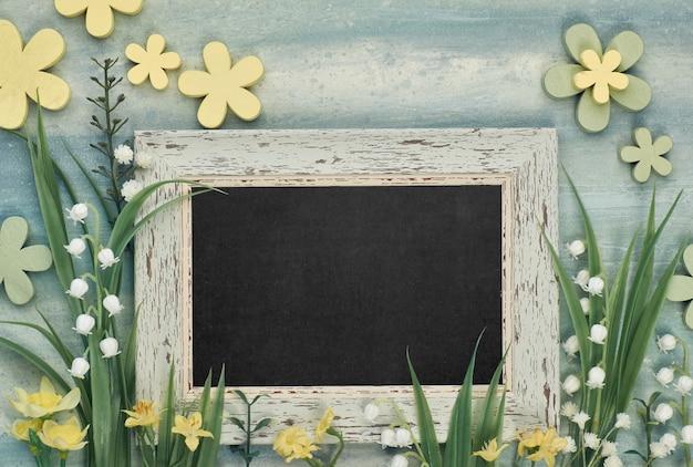 Доска в обрамлении весенних цветов на нейтральном фоне, место для вашего текста Premium Фотографии