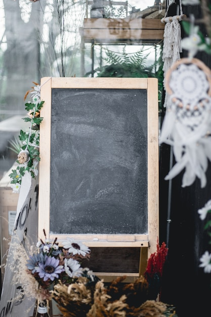 Blackboard in front of the cafe with flowers decorated around Premium Photo