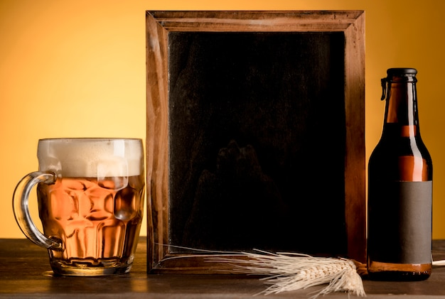 Blackboard and glass of beer and alcoholic bottle on wooden table Premium Photo