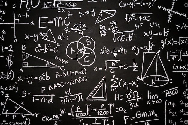 Blackboard inscribed with scientific formulas and calculations Free Photo