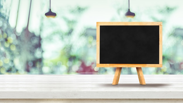 Blackboard menu on white plank wooden table top with blurred window of coffee shop Premium Photo