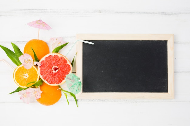 Blackboard near plant leaves and exotic fruits Free Photo