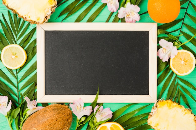 Blackboard near plant leaves with fresh fruits Free Photo