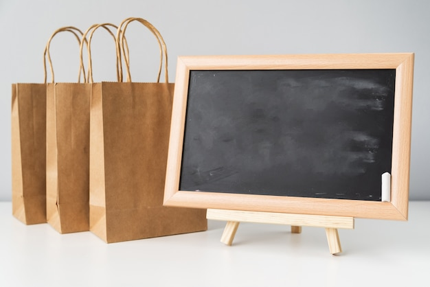 Blackboard near shopping bags Free Photo