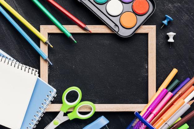 Blackboard slate with bright stationery Free Photo