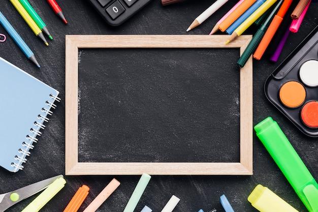Blackboard slate with colourful stationery Free Photo