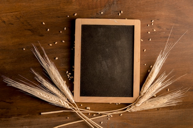 Blackboard and spike wheat on brown wooden table Free Photo