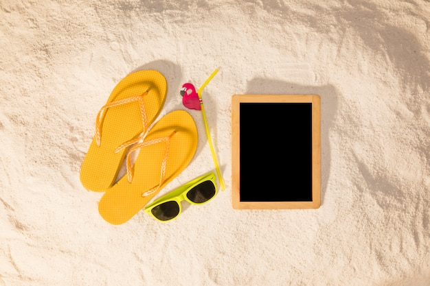 Blackboard and summer accessories on sand Free Photo