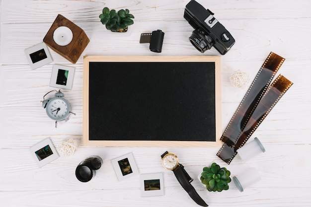 Blackboard surrounded by photography elements Free Photo