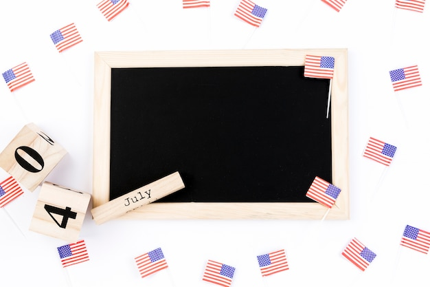 Blackboard on white background surrounded by small usa flags Free Photo