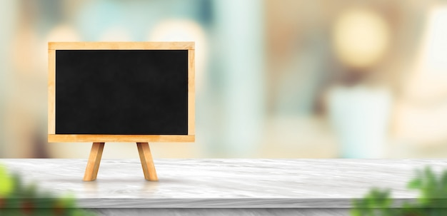Blackboard on white marble table and blurred soft light table in restaurant Premium Photo