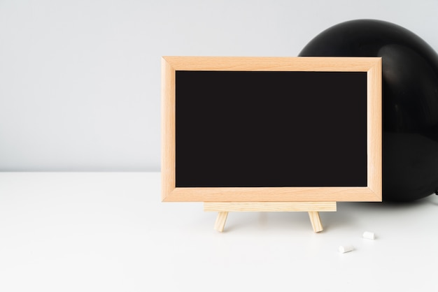 Blackboard with chalk in front of black balloon Free Photo