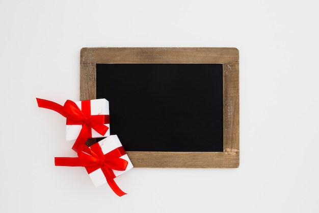 Blackboard with christmas gifts on white background Free Photo