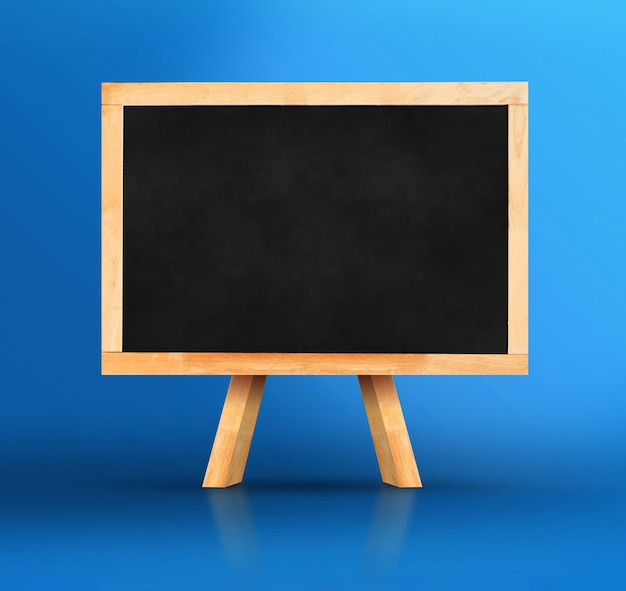 Blackboard with easel on vivid blue studio backdrop Premium Photo