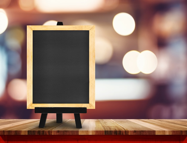 Blackboard with easel on wood table at blurred coffee shop Premium Photo