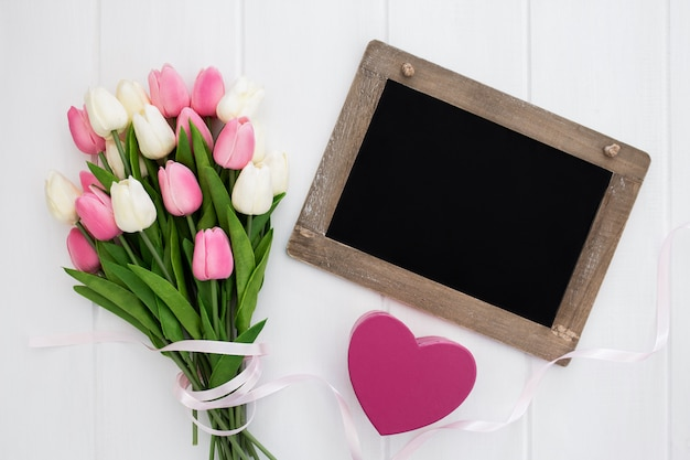 Blackboard with heart and bouquet of tulips Free Photo