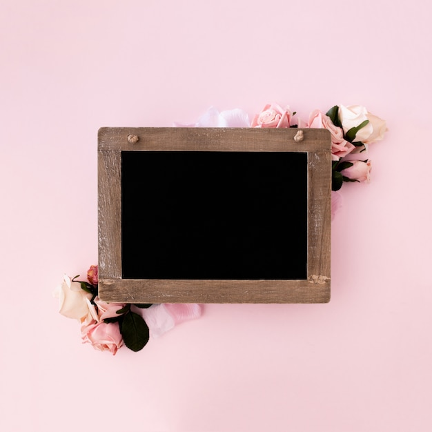 Blackboard with pink roses on pink background Free Photo