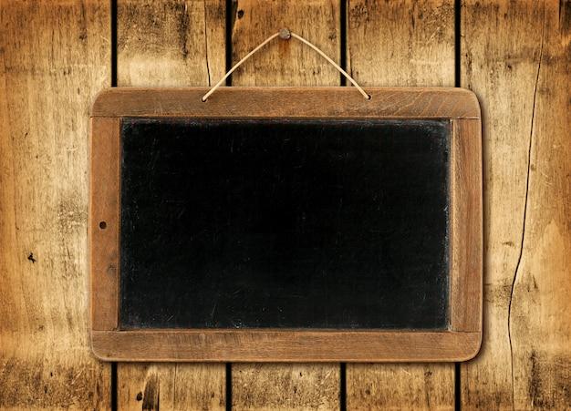 Blackboard on a wood wall background Premium Photo