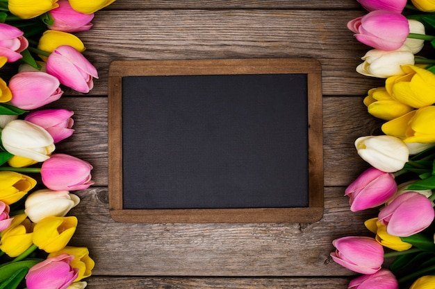 Blackboard on wooden with tulips Free Photo