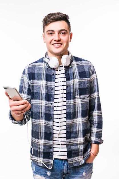 Черноволосый школьник слушает музыку, используя свой новый мобильный телефон Бесплатные Фотографии