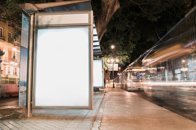 Blank advertisement billboard at bus stop with blurred traffic lights Free Photo
