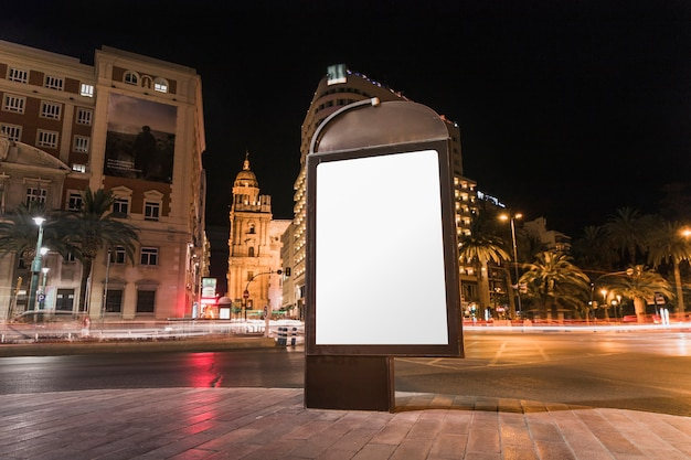 Blank advertisement billboard in front of building at night Free Photo
