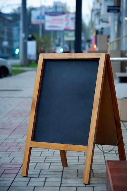 Blank advertising board on city street on blurred background. Premium Photo