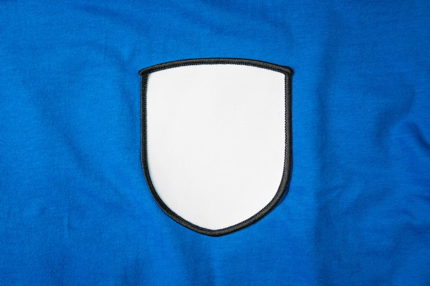 Blank arm patch on blue sport shirt. white team logo and emblem for your montage or edit. Premium Photo