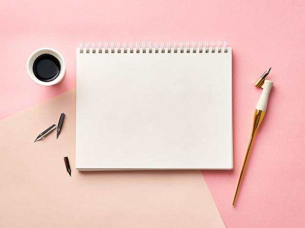 書道ペンとインクとピンクの背景の空白のアーティストスケッチブック。上からの眺め。 Premium写真