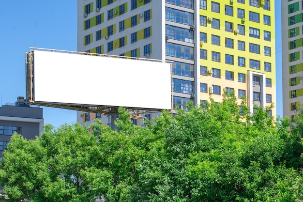 Blank billboard on the background of a building and green trees. mockup Premium Photo
