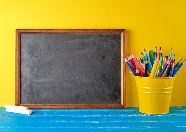 Blank black chalk frame, white chalk and school supplies Premium Photo