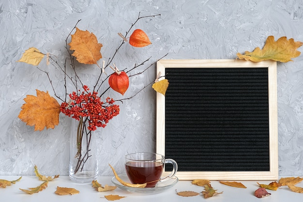 Blank black letter board frame and autumn bouquet of branches with yellow leaves on clothespins in vase Premium Photo