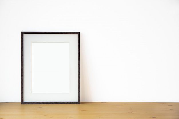 Blank black picture frame on the white wall and the wooden floor, template poster interior photo 3d background Premium Photo