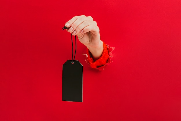 Blank black tag in female hand through a hole in red. price tag, gift tag, address label. Premium Photo