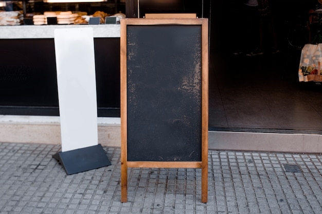 Blank blackboard menu and white billboard in front of the restaurant at street Free Photo