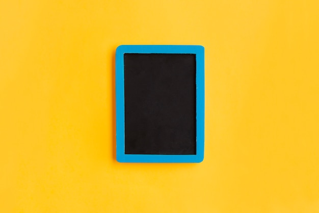 Blank blackboard  with blue wooden frame on yellow Free Photo
