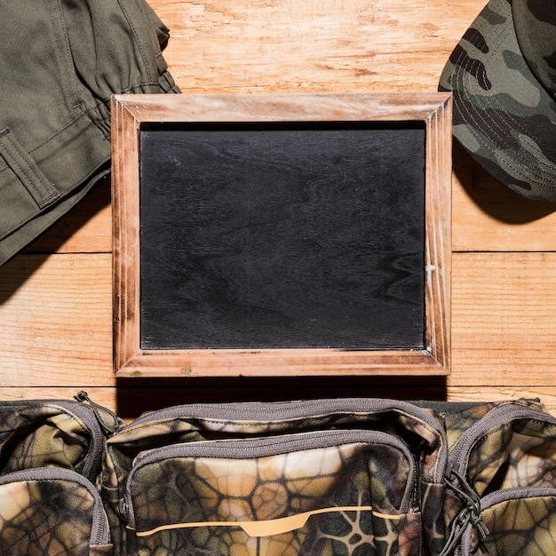 Blank blackboard with pants; bag and cap on wooden table Free Photo